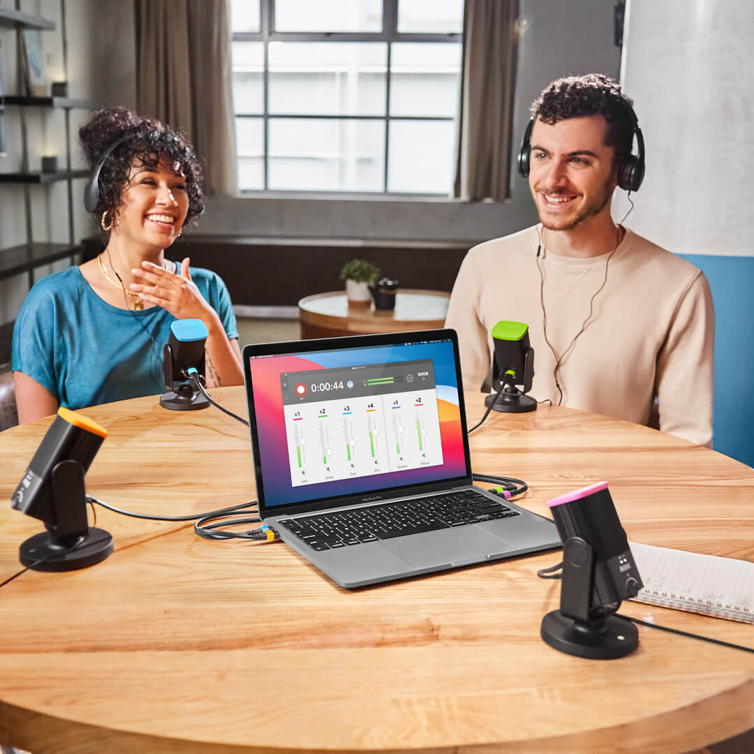 two people podcasting with Laptop with four microphones and colors