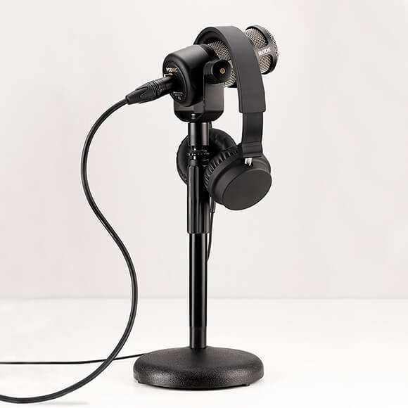 RODE PodMic connected to DS-1 desk stand with headphones attached and an XLR cable leading out of frame.
