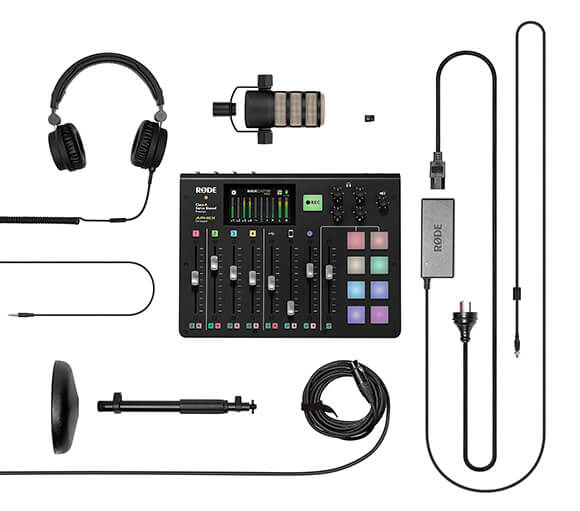 Flat lay containing RODECaster Pro, power cable, XLR cable, DS1 desk stand, headphones, PodMic and microSD card