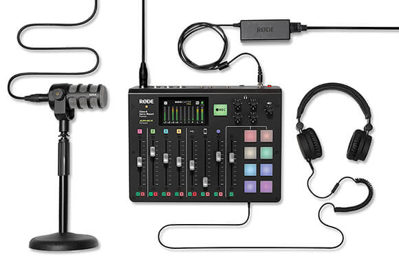 Flat lay of the RODECaster Pro, PodMic, DS1 desk stand, power cable, XLR cable and headphones all connected.