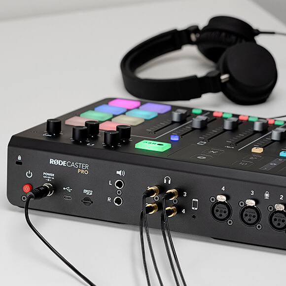 Four pairs of headphones connected to the back of the RODECaster Pro with HJA-4 connectors. One pair of headphones connected to the front of the RODECaster Pro.
