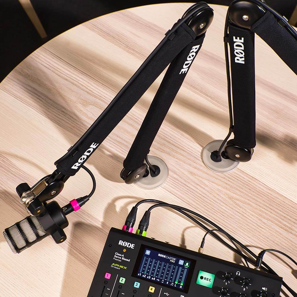 RØDE PSA1+ mounted into a desk with the threaded desk mount, positioning a PodMic plugged into the RØDECaster Pro.